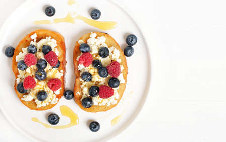 Sandwiches with curd cheese, blueberries, raspberries and honey on white plate. Healthy breakfast. Top view, flat lay 스톡 콘텐츠