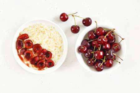Oatmeal porridge with cherry slices in bowl over white stone background. Top view, flat lay