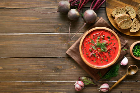 Traditional ukrainian russian soup (borscht). Beetroot soup in bowl on wooden background with copy space. Top view, flat lay