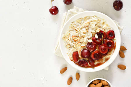 Healthy oatmeal porridge with cherry slices and nuts in bowl over white stone background with free text space. Top view, flat lay 스톡 콘텐츠