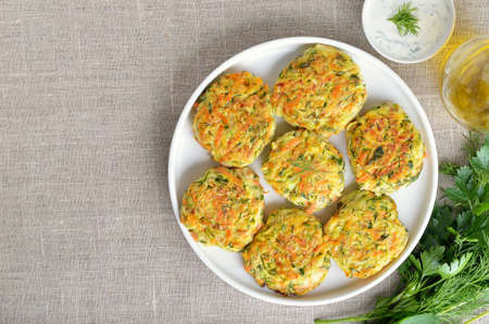 Tasty vegetable cutlets from zucchini, carrot, herbs on white plate. Top view, flat lay