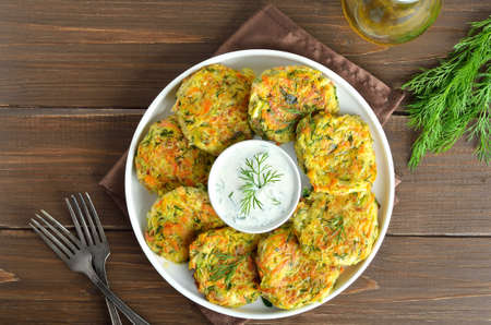 Diet vegetable cutlet from zucchini, carrot, herbs on wooden table. Healthy food. Top view, flat lay
