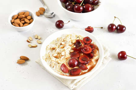 Porridge with cherry slices and nuts in bowl 스톡 콘텐츠