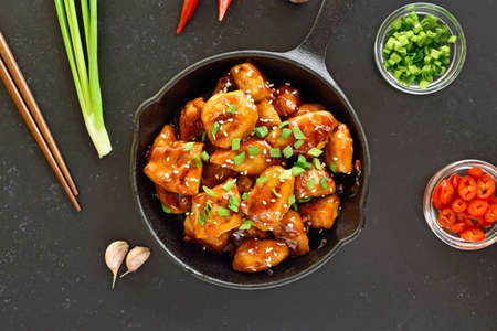 Easy teriyaki chicken in cast iron pan over black stone background. Top view, flat lay