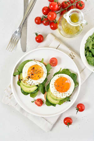 Bread with fried eggs, avocado and greens. Healthy breakfast. Top view, flat lay