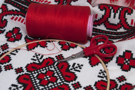 thread count: Cross-stitch canvas with red thread and accessories, macro shooting