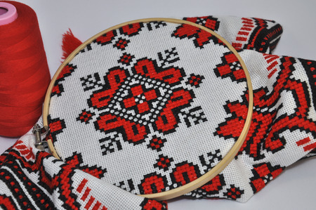 thread count: Embroidery on a white canvas with black thread in wooden hoop on a white background