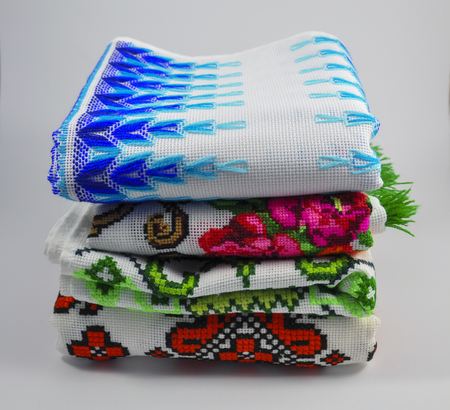 thread count: pile of embroidered towels on a white background