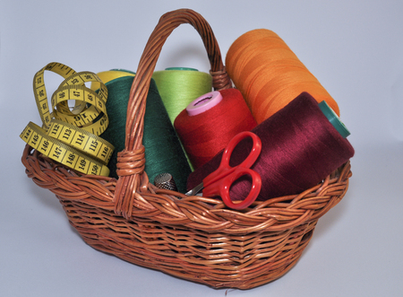 thread count: Set for sewing and embroidery in a wicker basket on a white background