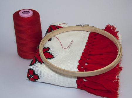 thread count: Traditional embroidered towel with red thread on white background with wooden hoop and coil red thread