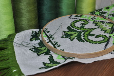 thread count: Embroidered towel traditional wooden hoop on the background of a wooden table
