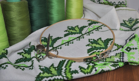 thread count: cross-stitch embroidery frame wooden towel in bright green thread Stock Photo