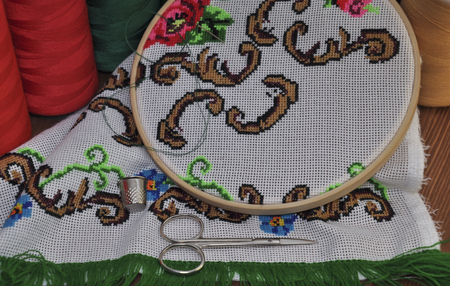 thread count: set of the hoop, scissors, multi-colored threads for embroidery on a wooden table