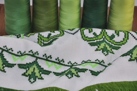 thread count: Traditional Ukrainian embroidered towel bright green thread in the hoop on the background of a wooden table