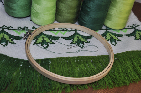 thread count: cross-stitch embroidery frame wooden towel in bright green thread on a background of a wooden table