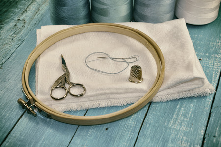 iron hoops: Items for embroidery on a wooden table, retro style photo Stock Photo
