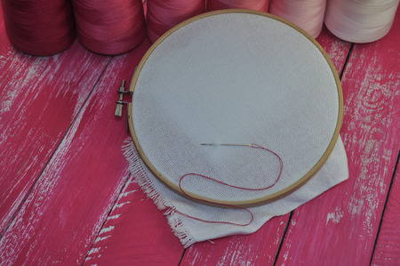iron hoops: canvas in wooden hoop for embroidery on a pink background wooden table