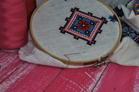 needlecraft product: product with a geometrical pattern cross on a background of pink wooden table