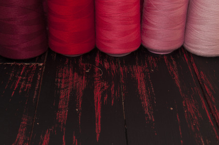 old spools: Spools of thread in the red range of sewing and needlework on the background of the old wooden table Stock Photo