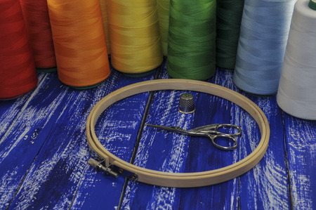 needlecraft product: Hoop, scissors and  threads for sewing and embroidery on the background of a wooden table Stock Photo