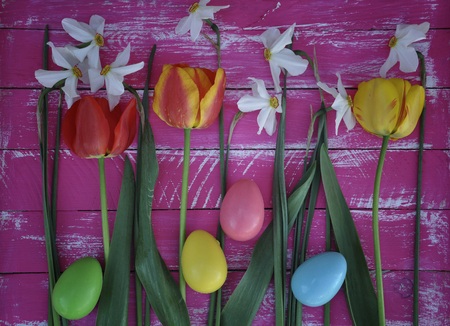 Tulips, narcissus and Easter eggs on background wooden table Stock Photo