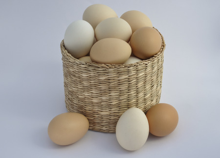 close out: Chicken eggs in a wicker basket on a white background, close out of the basket three eggs