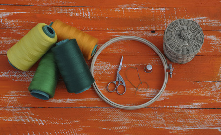 old items: threads in the coil and crafts items on the old wooden table orange Stock Photo