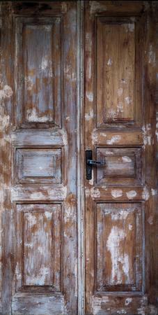 fanlight: brown old door with cracked paint and iron door handle