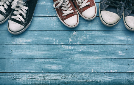 two pairs of men's sneakers and one pair of women's shoe on vintage background, toning