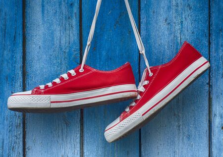 glamur: pair sneakers hanging on a wooden old retro blue background Stock Photo