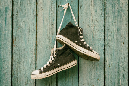 glamur: Dark blue sneakers hang on a nail on a blue wooden wall, canvas shoe,toning