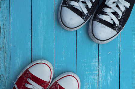 ingram: Red and blue sneakers on a blue wooden background, top view