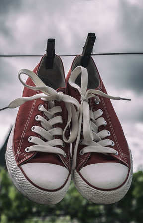 pair of red womens shoe drying on a rope, toned photo Stock Photo
