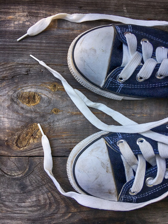 untied: Old worn blue sneakers with white laces untied on an old wooden surface Stock Photo