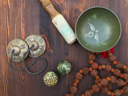 Tibetan singing bowl and objects for religious ritual, on a brown wooden background, top view