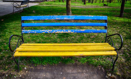 Old wooden bench with blue and yellow colors in the park is broken
