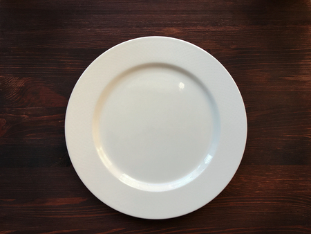 blank space: Empty white plate on wooden table, top view