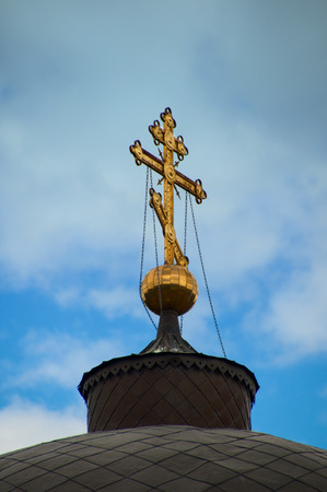 devote: Gold cross on the dome of the church against the blue sky Stock Photo