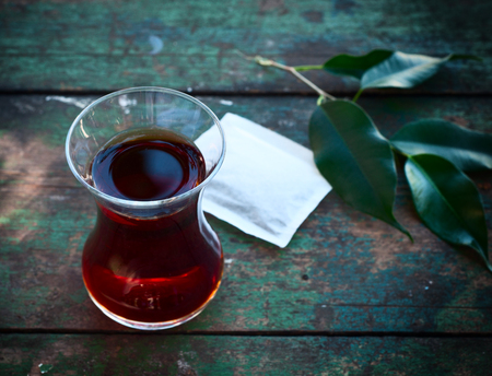 Turkish glass cup with black tea, near branch with leaves Stock Photo
