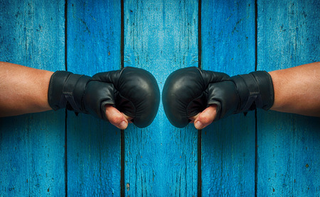 facing each other: two fists in boxing gloves facing each other on a background of blue wooden surface