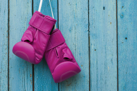 Pink boxing gloves on blue cracked wooden background, empty space on the right