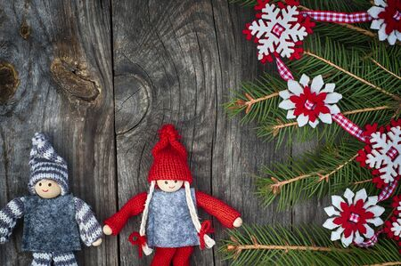 Christmas background with decorated fir branch and textile toys on gray wooden background