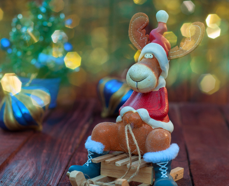 animal figurines: Reindeer on winter wooden sled, blurred bokeh background with multi-colored, wooden background Stock Photo