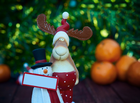 christmas elk: Figures Christmas elk and snowman with a sign on a background of blurry orange tangerine, christmas background Stock Photo