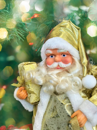 Christmas Santa Claus with a big white beard and dressed in a festive golden, behind the blurred background with colorful bokeh Stock Photo