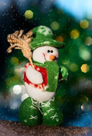 Textile snowman on a log, blurred background with a large multi-colored bokeh Standard-Bild