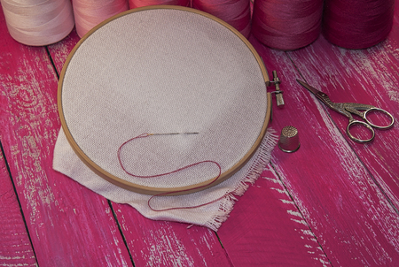 fancywork: Red and pink threads for sewing and embroidery, fabric in the wooden embroidery hoop