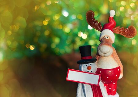 Christmas toy elk and snowman on green blurred background with bokeh Stock Photo