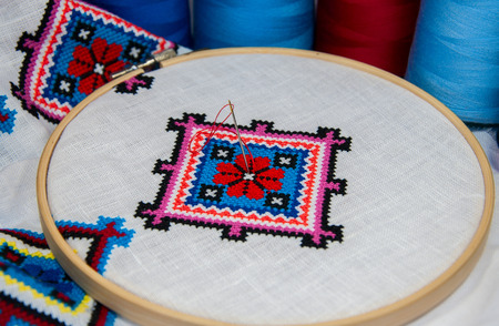 Traditional folk geometric pattern embroidered cross on a white cloth, near a number of colored thread
