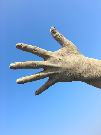 Womens human left hand in the splayed fingers of the hand in the dirt